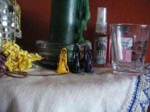 These dear little acrylic Muertitos came from Mexico via The Vodou Store (http://www.vodoustore.com/store/) I met the proprietors at PantheaCon and bought a few goodies, including a lovely prayer card. The La Flaca bottle in the background is also from them.